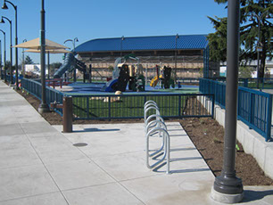 Photo of new bike rails, water fountain, park with slides, swings, and playgrounds